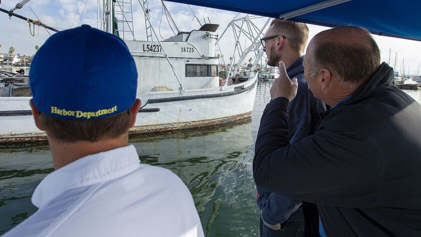 Tommy Tupman, left, with Newport Beach Harbor Services shows Zack, and Brent Beasley an old 34-foot
