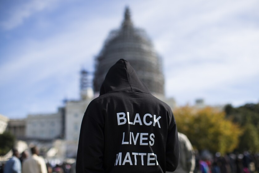 "A man wears a hoodie which reads, ""Black Lives Matter"" as he stands on Capitol Hill in Washington during a rally on Oct. 10, 2015."