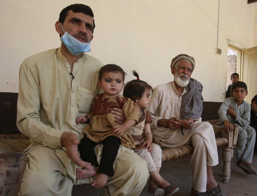 In this May 6, 2020 photo, Tariq Nawaz holds his 10-month-old baby daughter Tuba who suffers from polio, in Suleiman Khel, Pakistan. For millions of people like Nawaz who live in poor and troubled regions of the world, the novel coronavirus is only the latest epidemic. They already face a plethora of fatal and crippling infectious diseases: polio, Ebola, cholera, dengue, tuberculosis and malaria, to name a few. The diseases are made worse by chronic poverty that leads to malnutrition and violence that disrupts vaccination campaigns. (AP Photo/Muhammad Sajjad)