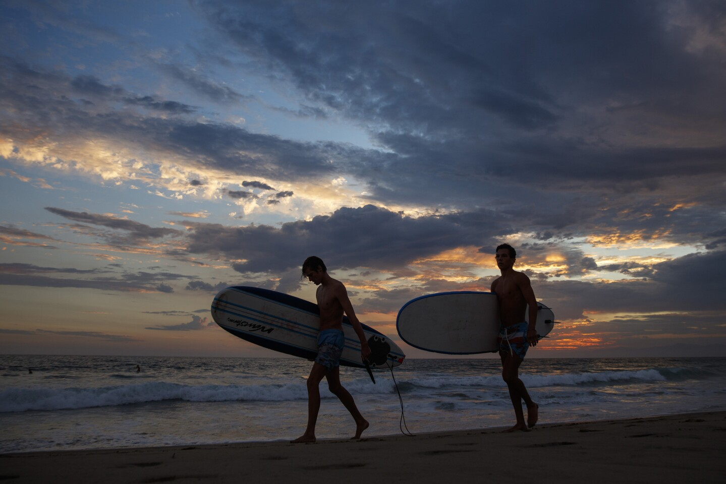 Brady Webush, left, and Johnny Byrne, both from Manhattan Beach, end their day in the El Porto area of Manhattan Beach. Weather in Los Angeles brought morning showers to the beaches and thunderstorms to other parts of L.A. County.