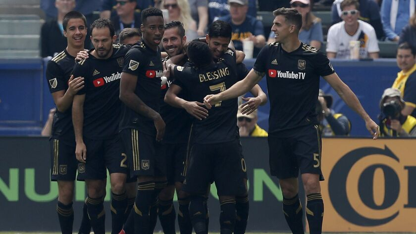 LAFC forward Carlos Vela, second from right, is congratulated by teammates after scoring the first of his two first half goals against the Galaxy on Mar. 31 at StubHub Center.