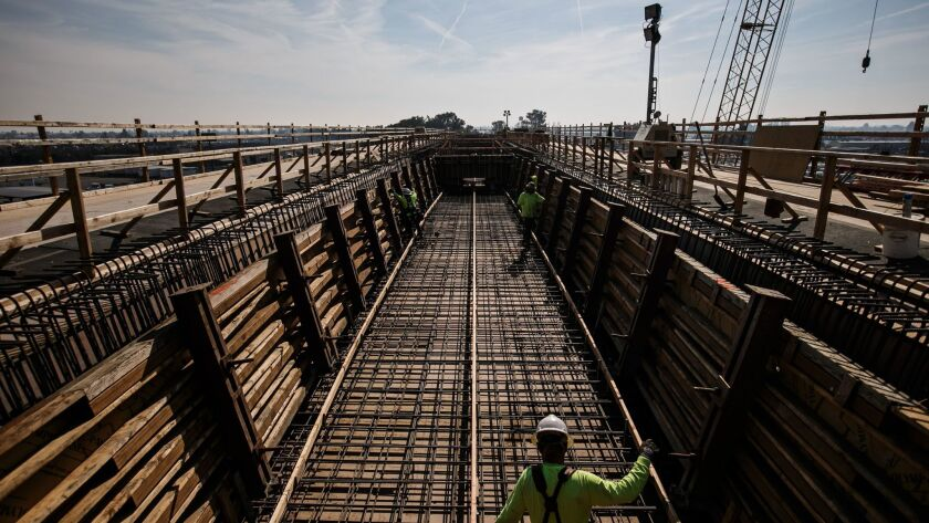 Construction workers at a viaduct being built to extend over State Route 99 and North and Cedar Avenues in Fresno County.