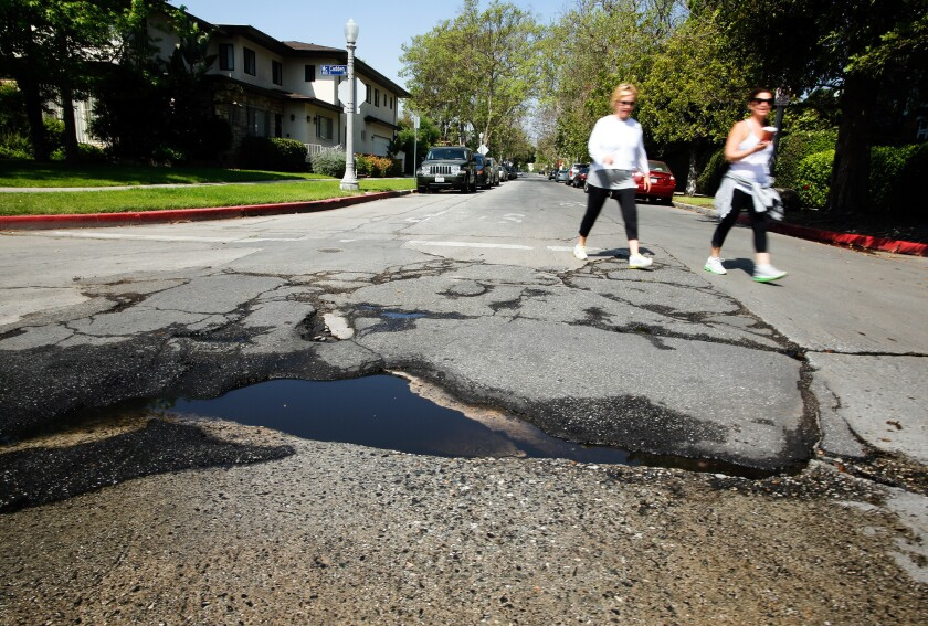 Pedestrians walk near a pothole at McCadden Place and 4th Street in Hancock Park.