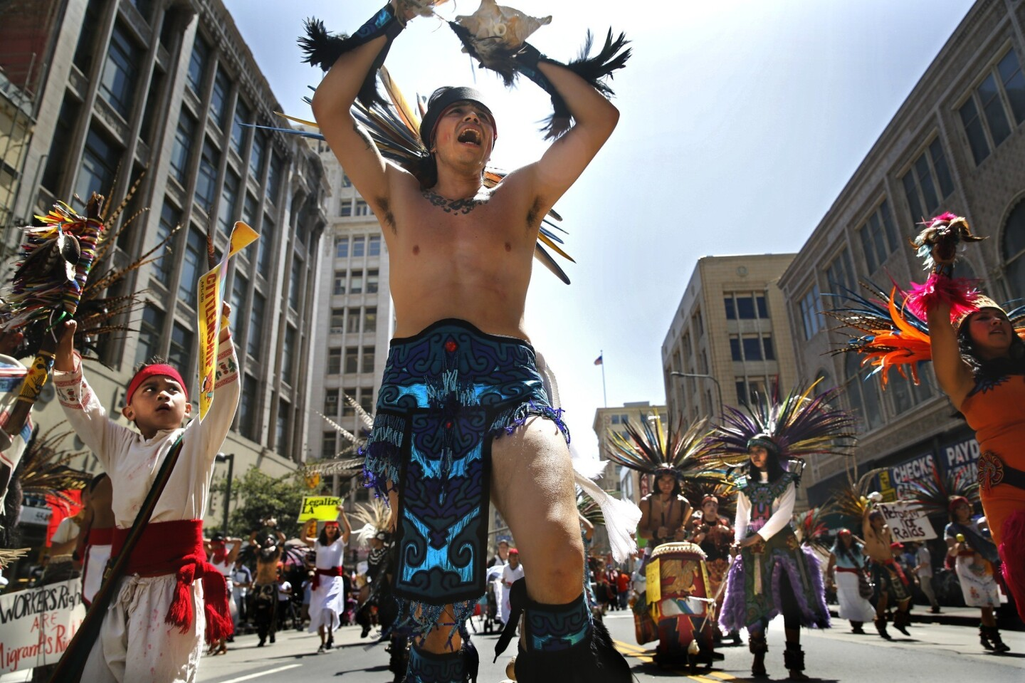 Costumed members of the Danza Mexica Cuauhtemoc political Aztec dance group perform on Broadway in downtown L.A. earlier this month.