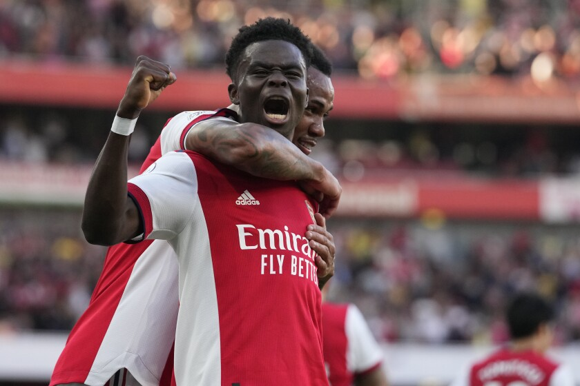Arsenal's Bukayo Saka, front, celebrates after scoring his side's third goal during the English Premier League soccer match between Arsenal and Tottenham Hotspur at the Emirates stadium in London, Sunday, Sept. 26, 2021. (AP Photo/Frank Augstein)