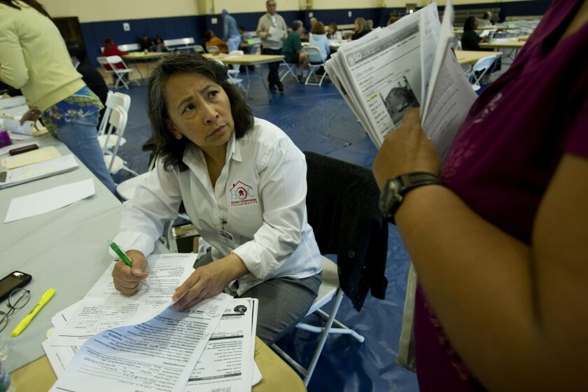 A struggling homeowner gets advice from housing counselor Faith Espejo, pictured, at a March 2012 foreclosure-prevention clinic put on by San Diego non-profit Housing Opportunities Collaborative. The group will set up computer terminals throughout the county by summer to connect homeowners and rent