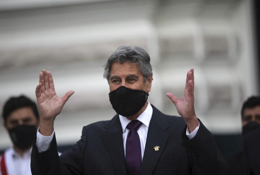 El legislador centrista Francisco Sagasti saluda a la multitud en las afueras del edificio legislativo