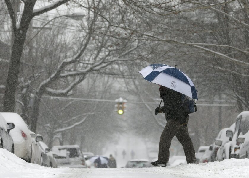 FILE - This Jan. 5, 2014 file photo shows a pedestrian walking in the snow in the Center Square neighborhood in Albany, N.Y. America's Midwest and East keep getting battered by cold and storms. Atlanta has been paralyzed by snow. California has been bone dry. And the National Weather Service office in Alaska, where record warm temperatures were set, tweeted that it wants its cold weather back. (AP Photo/Mike Groll, File)