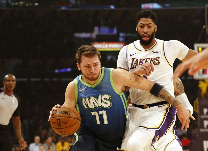 Dallas Mavericks guard Luka Doncic drives around Lakers forward Anthony Davis during the first half.