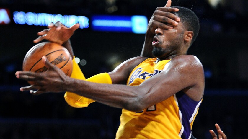 Lakers center Roy Hibbert gets hit in the face as he is fouled by Timberwolves center Gorgui Dieng in the third quarter.