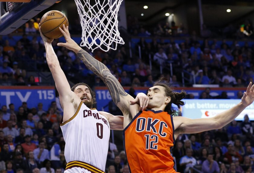 Cleveland Cavaliers forward Kevin Love (0) shot is blocked by Oklahoma City Thunder center Steven Adams (12) on the way to the basket during the second quarter of an NBA basketball game in Oklahoma City, Sunday, Feb. 21, 2016. (AP Photo/Alonzo Adams)