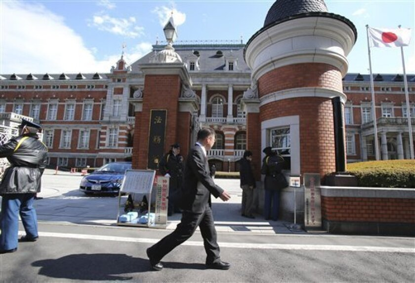 A man walks in front of the Justice Ministry in Tokyo Thursday, Feb. 21, 2013. The ministry said Japan executed early Thursday three inmates convicted of murder in its first executions under the government that took office in December.  Executions in the country are done by hanging. (AP Photo/Koji