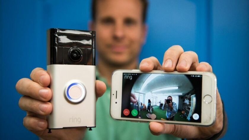 Ring founder and chief executive Jamie Siminoff holds a Ring Video Doorbell, left, that has a video camera so residents can see who's knocking with a smartphone app.
