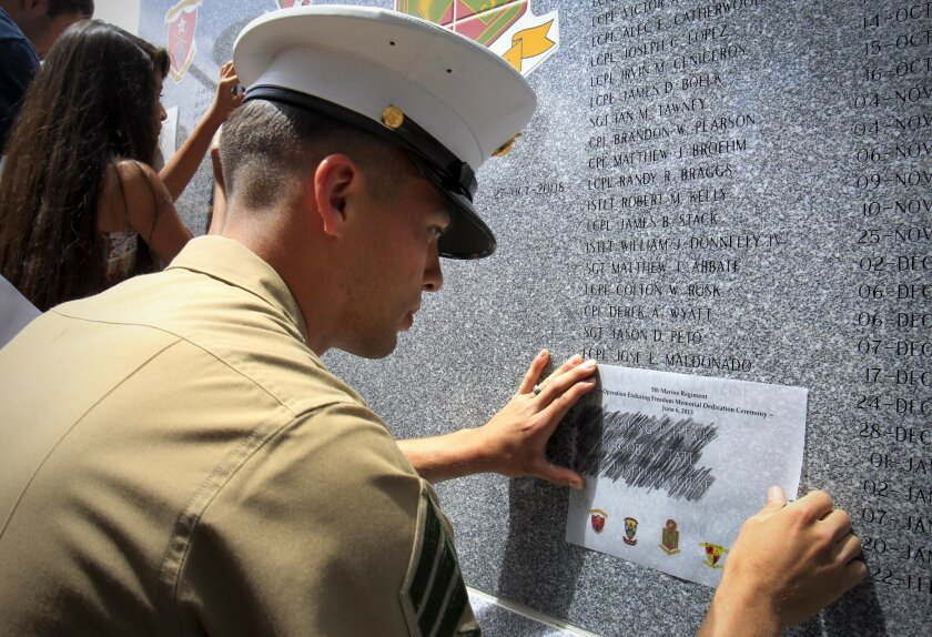 Marine Corps Sgt. Taylor Hartman creates pencil rubbings of  Marines he served with, during a memorial ceremony and unveiling of a monument to the 89 Marines killed during Operation Enduring Freedom, 2008-2012, at ceremony at Camp Pendleton.