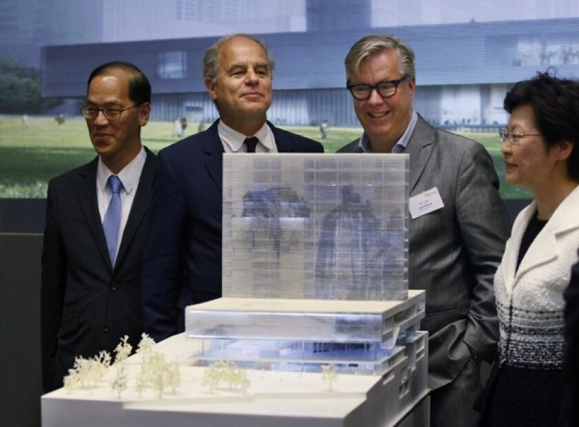 Hong Kong Secretary for Home Affairs Tsang Tak-sing, left, architect Pierre de Meuron, cultural district Executive Director Lars Nittve and Hong Kong Chief Secretary Carrie Lam with a model of M+ museum in Hong Kong.