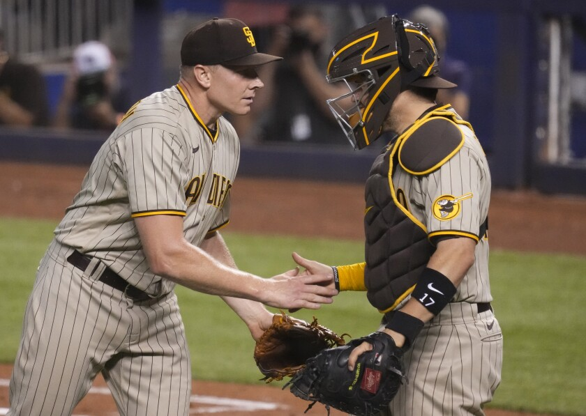 Mark Melancon and Victor Caratini celebrate the Padres' win against the Miami Marlins