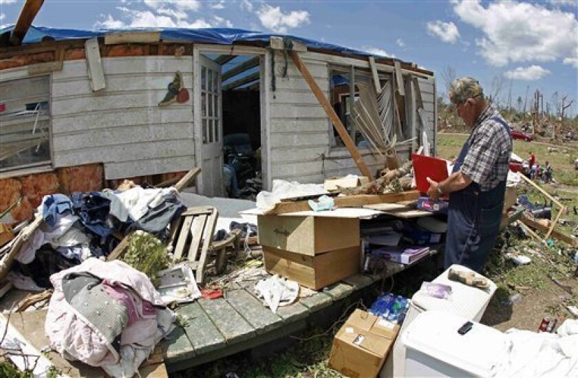 In this photo taken Friday, April 29, 2011, Marvin Quinn looks though a notebook after his home was destroyed by a tornado in Apison, Tenn. (AP Photo/Wade Payne)