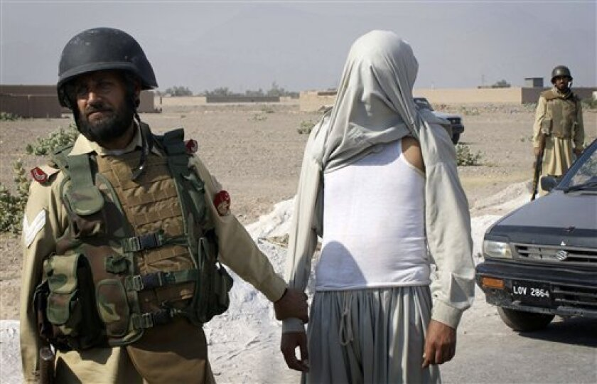 Soldiers of Pakistan para-military force arrest a suspect militant during a crack down operation in Pakistani tribal area of Khyber near Peshawar, Pakistan on Friday, Oct. 30, 2009. According to official, at least 32 suspected people were arrested by the security forces as a result of search operations at Shakas area against the militants. (AP Photo/Qazi Tariq)