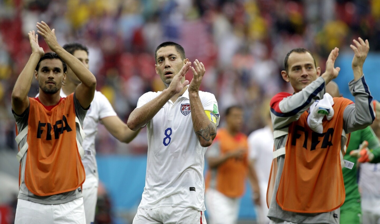 U.S. forward Clint Dempsey, center, celebrates with his teammates after advancing to the Round of 16 at the World Cup. The U.S. advanced despite the team's 1-0 loss to Germany in their final match of Group G play.