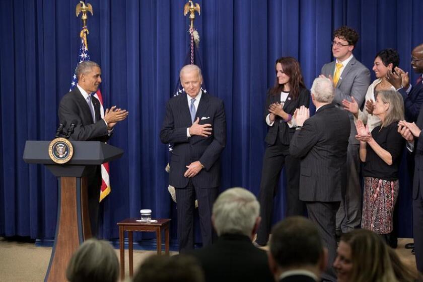 El presidente de Estados Unidos, Barack Obama (i), firma la Ley de Curación del Siglo 21, junto al vicepresidente estadounidense Joe Biden (c), los legisladores y simpatizantes del Edificio de la Oficina Ejecutiva de Eisenhower, hoy, martes 13 de diciembre de 2016, en Washington DC, (EE.UU.). EFE