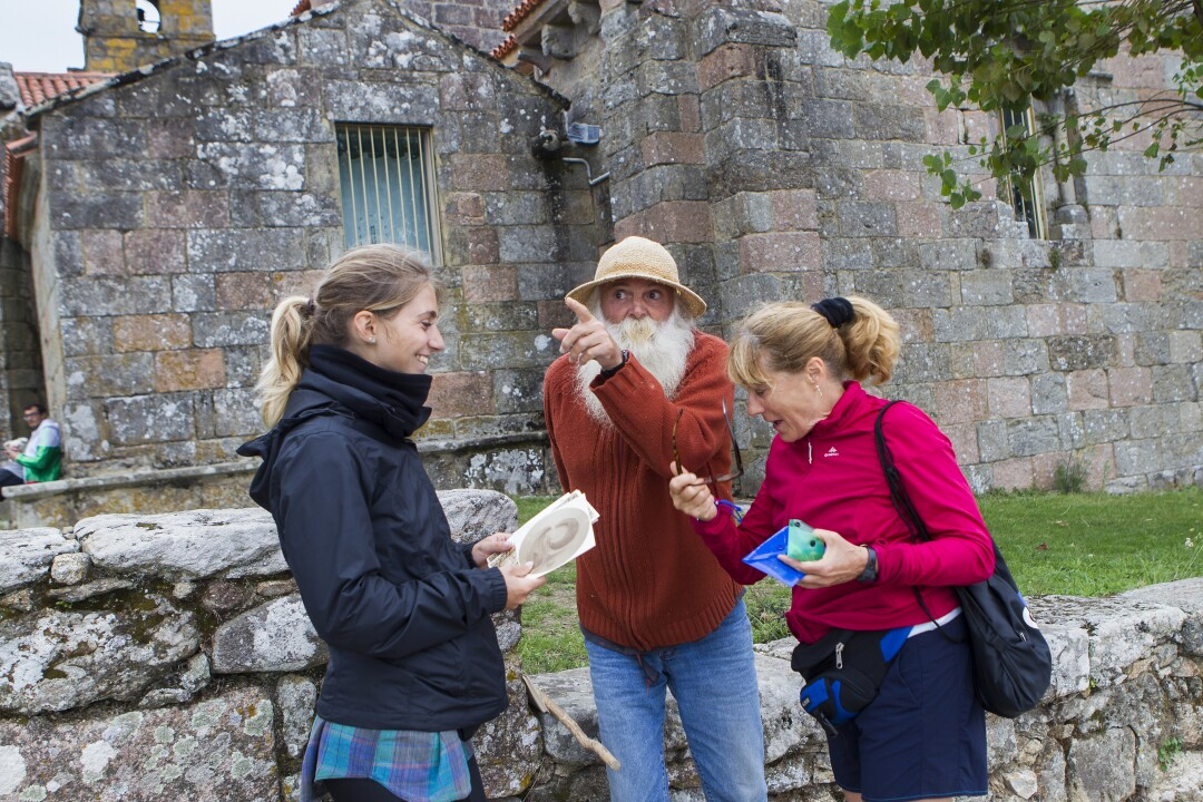 Pedro, a French pilgrim who lives in Fisterra, chatting with two tourists in front of the Santa María de Areas church