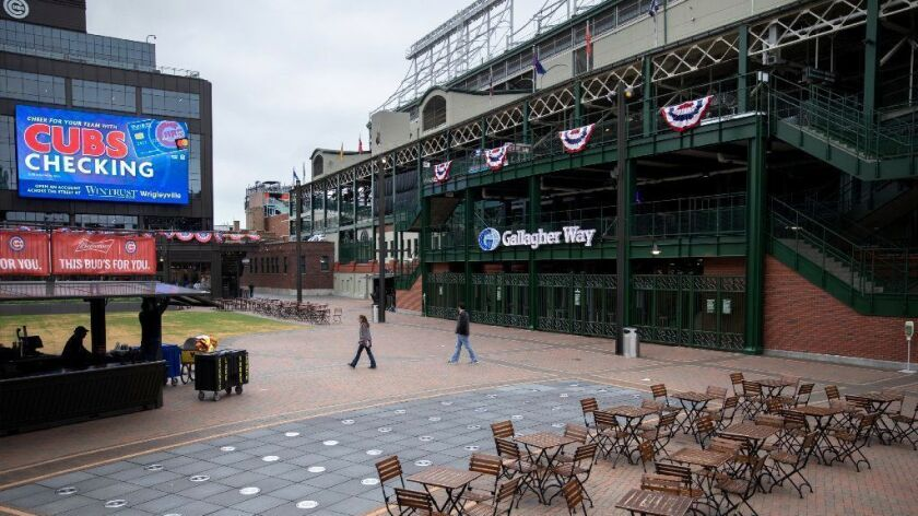 People walk through the Gallagher Way plaza next to Wrigley Field on Tuesday.