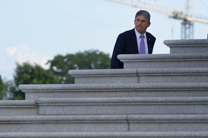 Sen. Joe Manchin, wearing a lavender tie, walks up the steps to the U.S. Capitol.