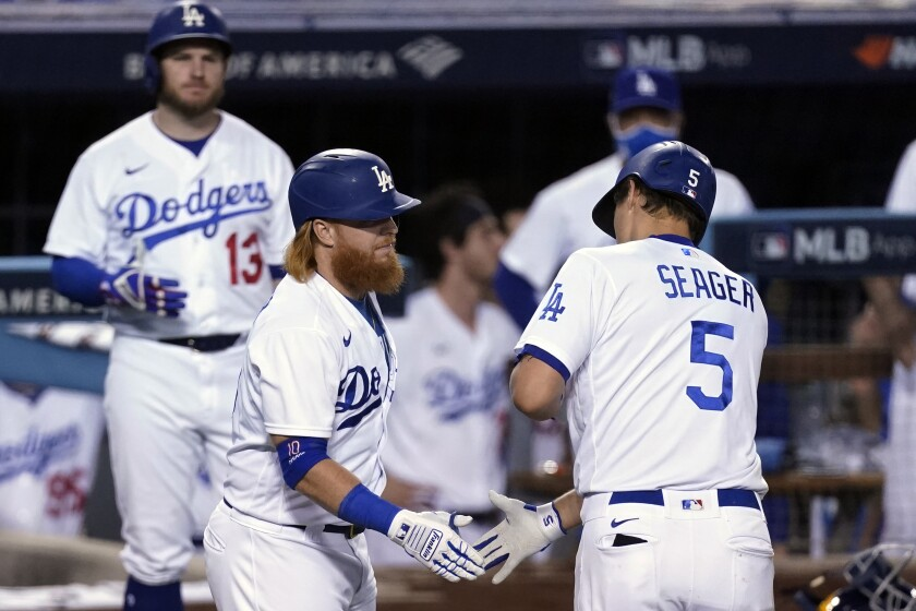 Dodgers' Corey Seager is met at home plate by Justin Turner.
