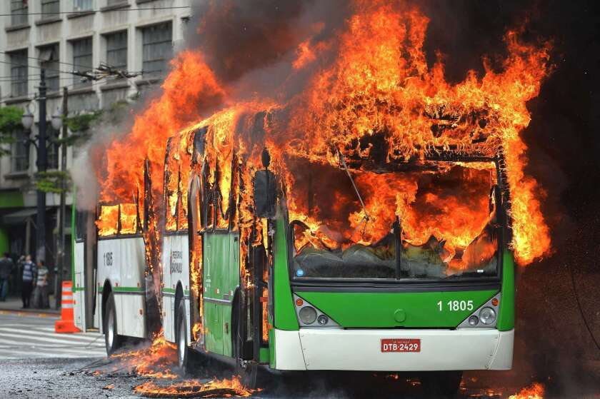 A bus burns Tuesday after being set ablaze during clashes between riot police and people squatting in a building in Sao Paulo, Brazil.