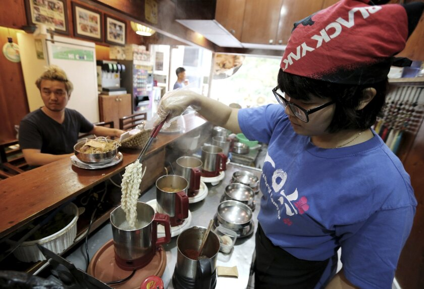 """In this Aug. 19. 2014 photo, a cook prepares """"ramyeon"""" instant noodles for Han Seung-youn, left, during an interview at a ramyeon restaurant in Seoul, South Korea. Instant noodles are an essential, even passionate, part of life for many in South Korea and other Asian countries. Hence the emotional"""