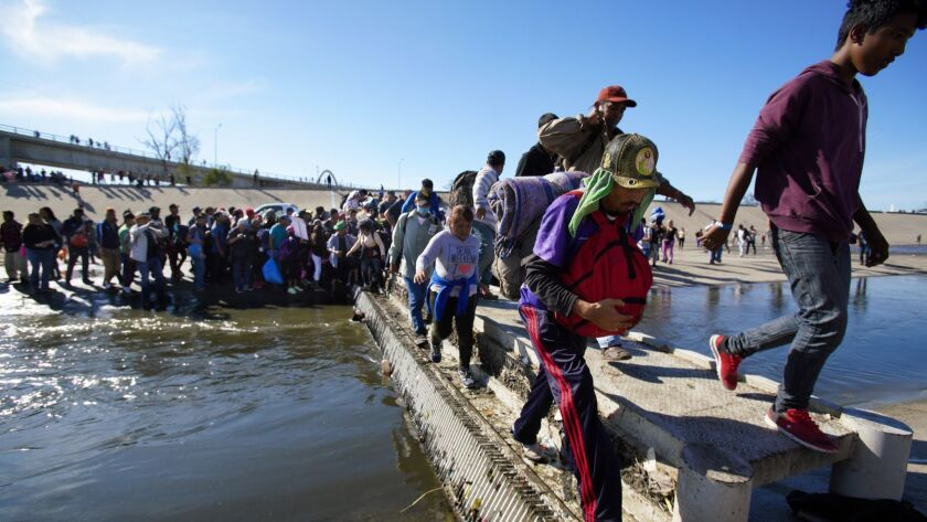 Migrants with the Central American caravan breach police line set up by the Mexico Federal Police, then access to the flood channel where they crossed to the north side of the flood channel.