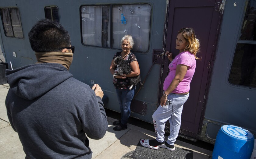 Three people outside a motorhome in South L.A.
