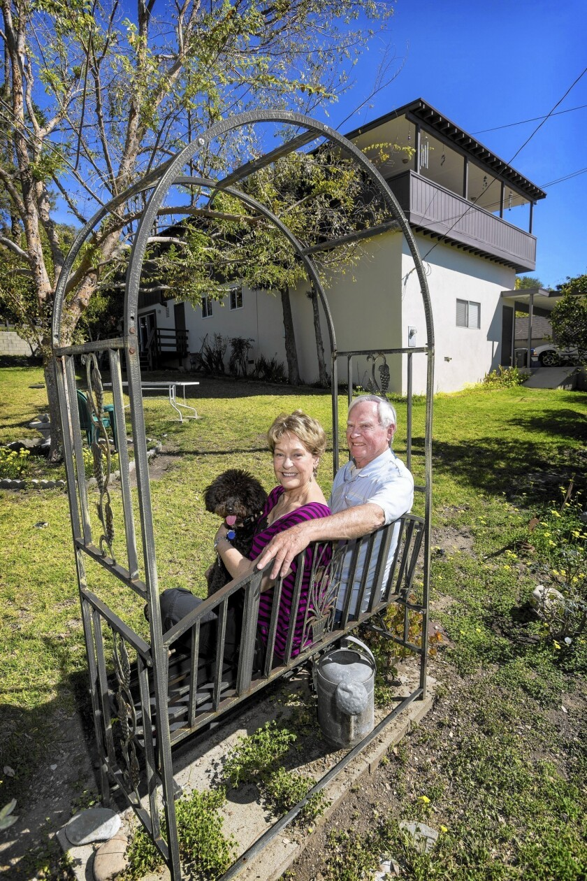 Retirees Wana and Owen Klasen, holding their dog Jager, at their home in Fillmore in Ventura County. They recently got a home equity line of credit that they used to paint and re-roof their house. They couldn't qualify for the credit line last year, but rising home prices made it possible this year.