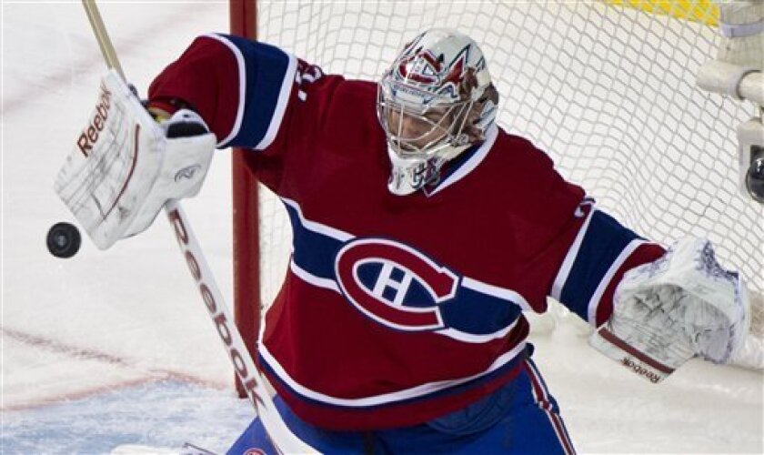 Montreal Canadiens goalie Carey Price deflects a Winnipeg Jets shot during the first period of an NHL hockey game Sunday, Feb. 5, 2012, in Montreal. (AP Photo/The Canadian Press, Paul Chiasson)