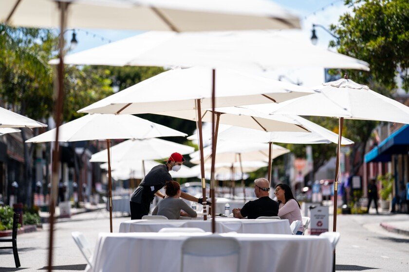 A worker at a San Pedro restaurant serves diners at a sidewalk table under umbrellas on May 29.