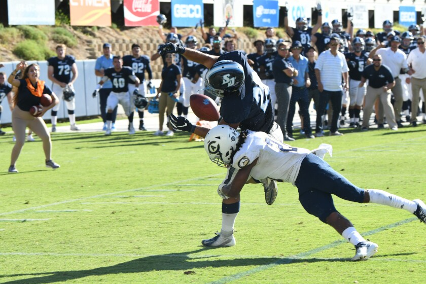 USD running back Emilio Martinez is hit in the final seconds and fumbles out of the back of the end zone Saturday against UC Davis.
