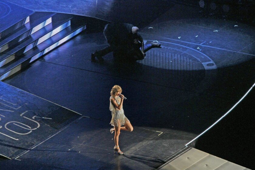 Security guards subdue a man, identified as Christian Ewing, who jumped onstage during the Taylor Swift concert at Petco Park on Aug. 29, 2015.