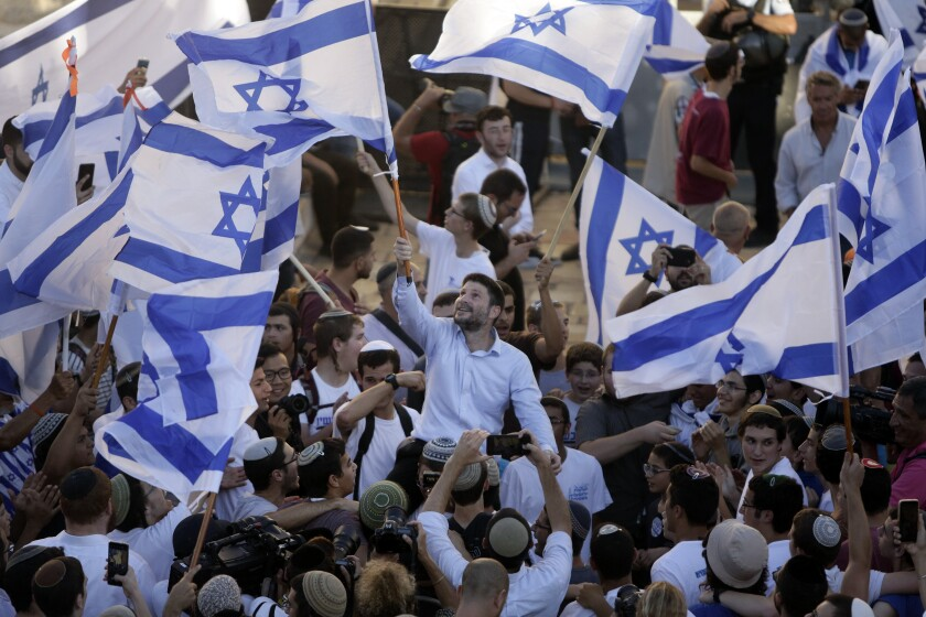 """Israeli Knesset members Bezalel Smotrich, center, waves an Israeli flag together with other Jewish ultranationalists during the """"Flags March"""" next to Damascus gate, outside Jerusalem's Old City, Tuesday, June 15, 2021. (AP Photo/Mahmoud Illean)"""