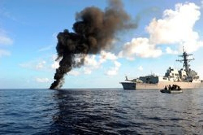 USS Farragut passes by a suspected pirate skiff that it had just disabled in the Indian Ocean in 2010. This image won the Military Photography (MILPHOG) award.) Courtesy of MC1 Cassandra Thompson/U.S. Navy