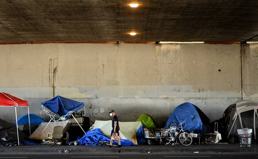A man walks by a homeless encampment on Venice Boulevard under the 405 Freeway. A federal judge has ordered the city and county of Los Angeles to relocate thousands of homeless people living near freeways starting on Friday.