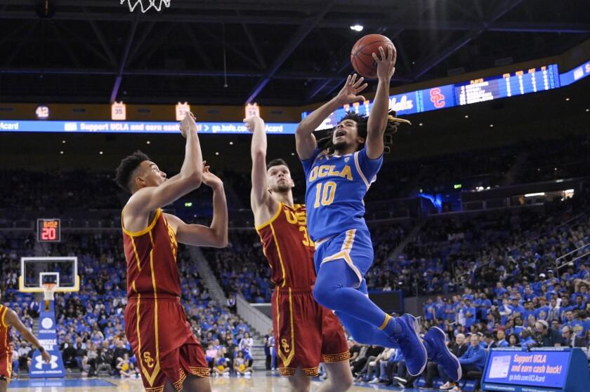 UCLA guard Tyger Campbell shoots as USC forward Isaiah Mobley and forward Nick Rakocevic defend.