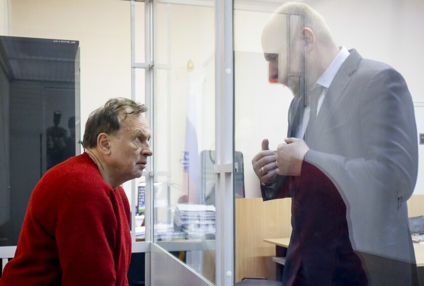 Oleg Sokolov, a history professor at St. Petersburg State University, left, listens to his lawyer sitting in a cage waiting for a court session in St. Petersburg, Russia, Monday, Nov. 11, 2019. The lawyer for a prominent Russian history professor suspected of murdering a female student, some of whose remains were found in his residence, is asking for him to be released under house arrest pending trial. The case of Oleg Sokolov has attracted wide attention in Russian media because of its grisly drama. (AP Photo/Dmitri Lovetsky)
