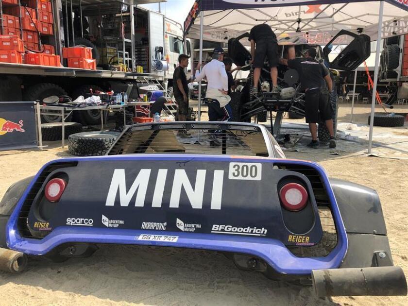 El vehículo del piloto español Carlos Sainz (Mini) es sometido a reparaciones contrarreloj para poder participar en la novena etapa del rally Dakar hoy en Piso (Perú). EFE