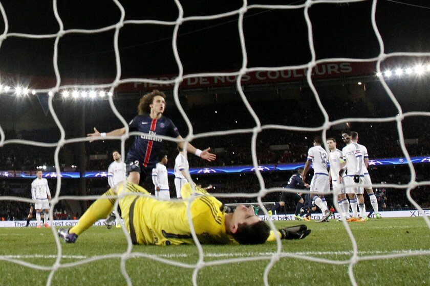 PSG's David Luiz celebrates teammate Zlatan Ibrahimovic's goal while Chelsea goalkeeper Thibaut Courtois lies down on the pitch during the Champions League round of 16, 1st leg soccer match between Paris Saint Germain and Chelsea at the Parc des Princes stadium in Paris, France, Tuesday, Feb. 16, 2