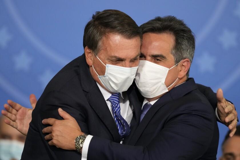 El presidente brasileño Jair Bolsonaro, a la izquierda, abraza a su nuevo jefe de gabinete, Ciro Nogueira, durante la ceremonia de su juramentación el miércoles 4 de agosto de 2021 en el palacio presidencial de Planalto, en Brasilia. (AP Foto/Eraldo Peres)