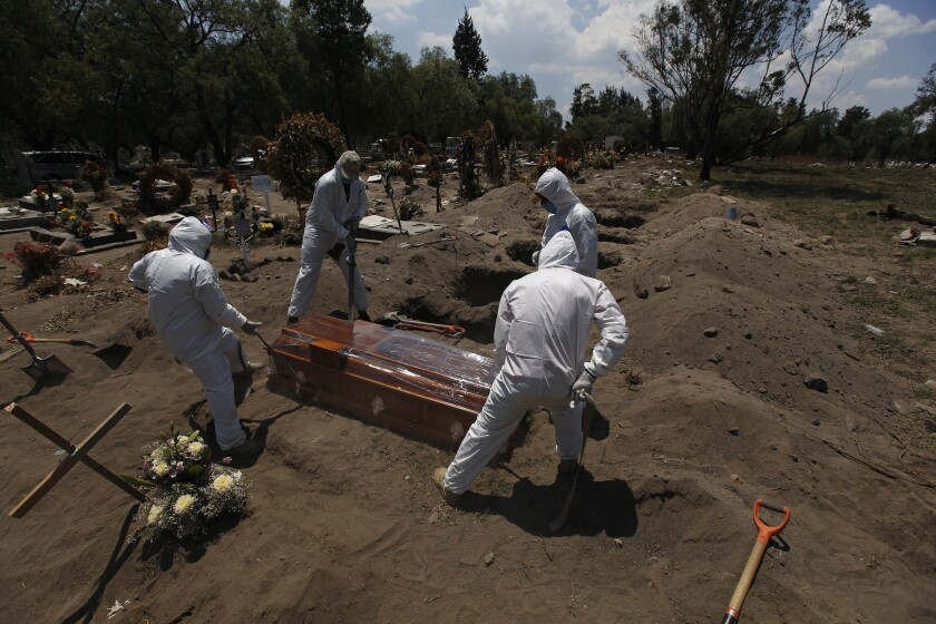 Cemetery workers in protective gear lower a coffin containing a COVID-19 victim in Mexico City.