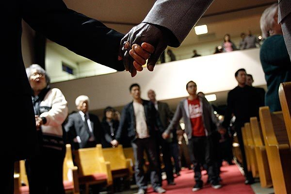 Mourners hold hands in during a vigil for victims of the Oikos University shootings at Oakland's Allen Temple Baptist Church on Tuesday.