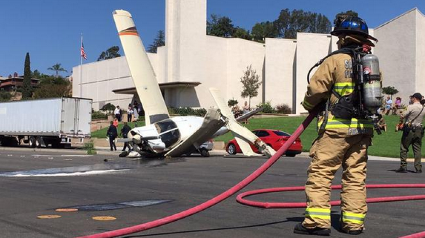 Crews keep an eye on spilled fuel after a small plane crashed near a church in a El Cajon neighborho