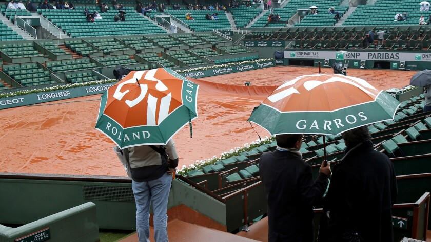 Spectators check out a court at Roland Garros after French Open play was postponed Monday.