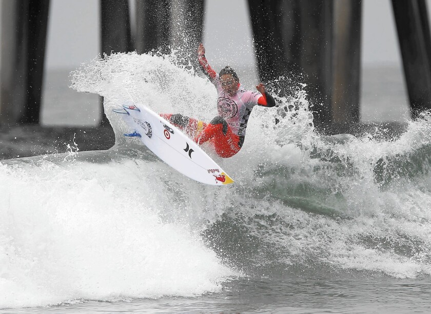 Hawaii's Carissa Moore pops a fins-free tail slide off the top of a set wave as she surfs in the women's championship final of the 2013 Van's US Open of Surfing at the Huntington Beach Pier, Sunday. Moore went on to win the championship final.